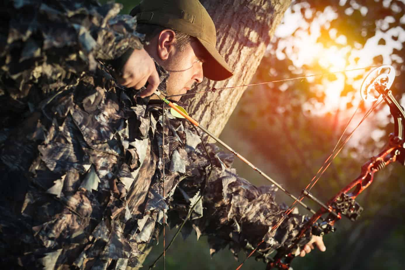 Man bow hunting in green camo