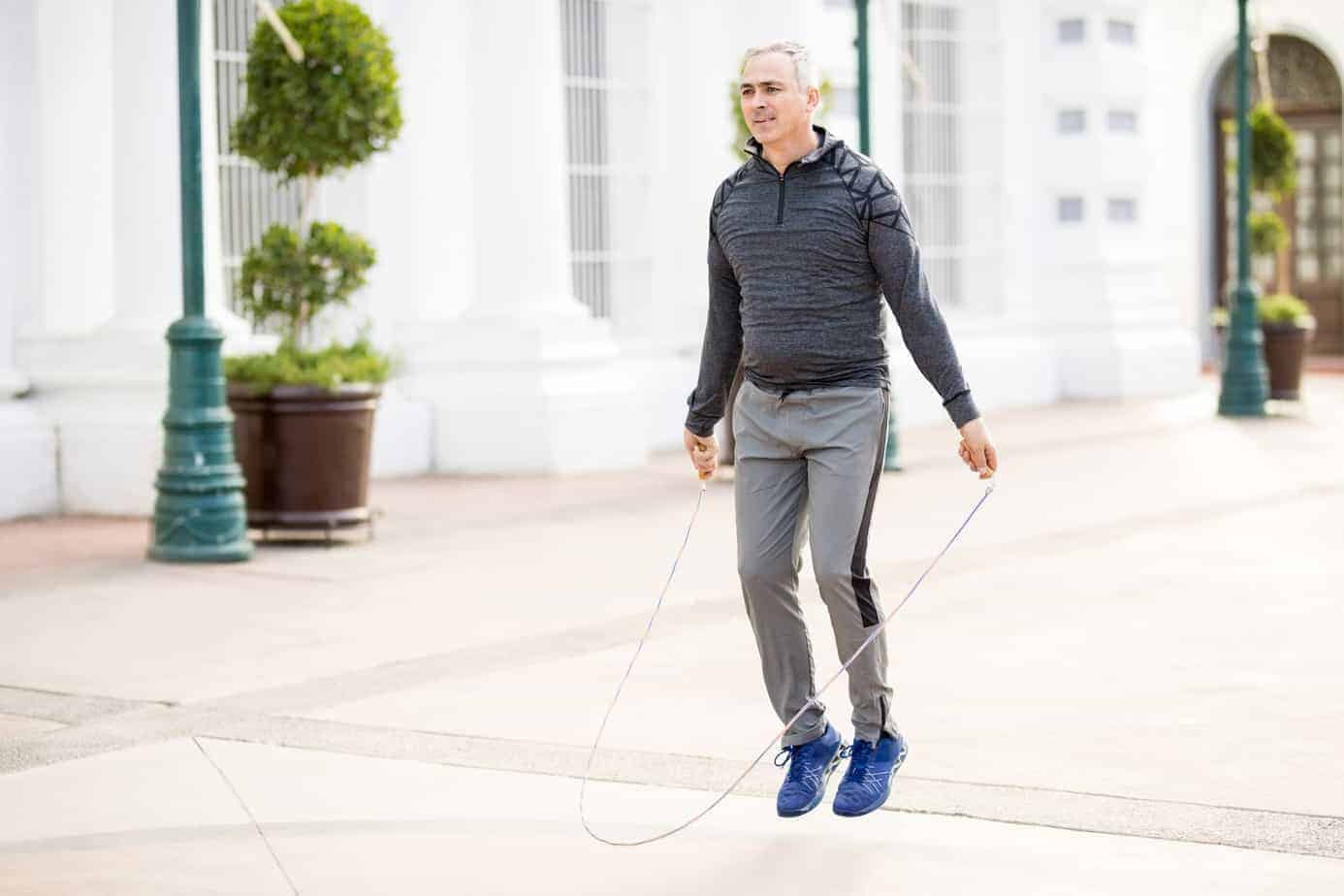 Mature man jumping a rope and exercising outdoors.