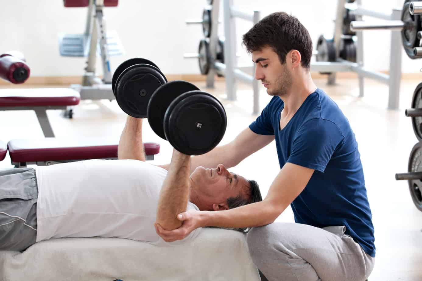 young man helping father dumbbell bench press