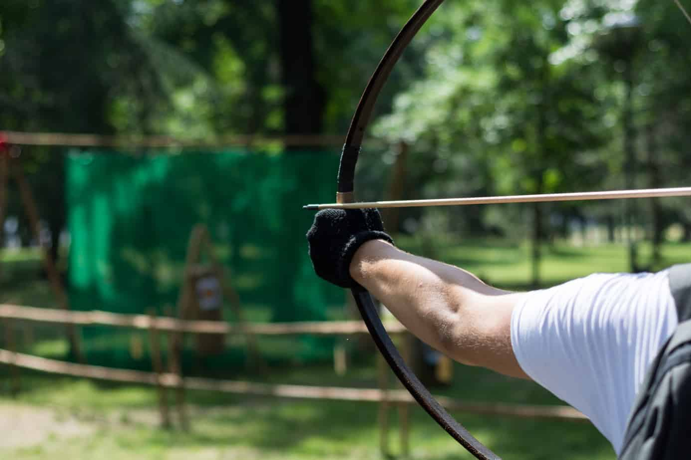 Archer hands with wooden bow shoot arrow. Archery tournament in forest.