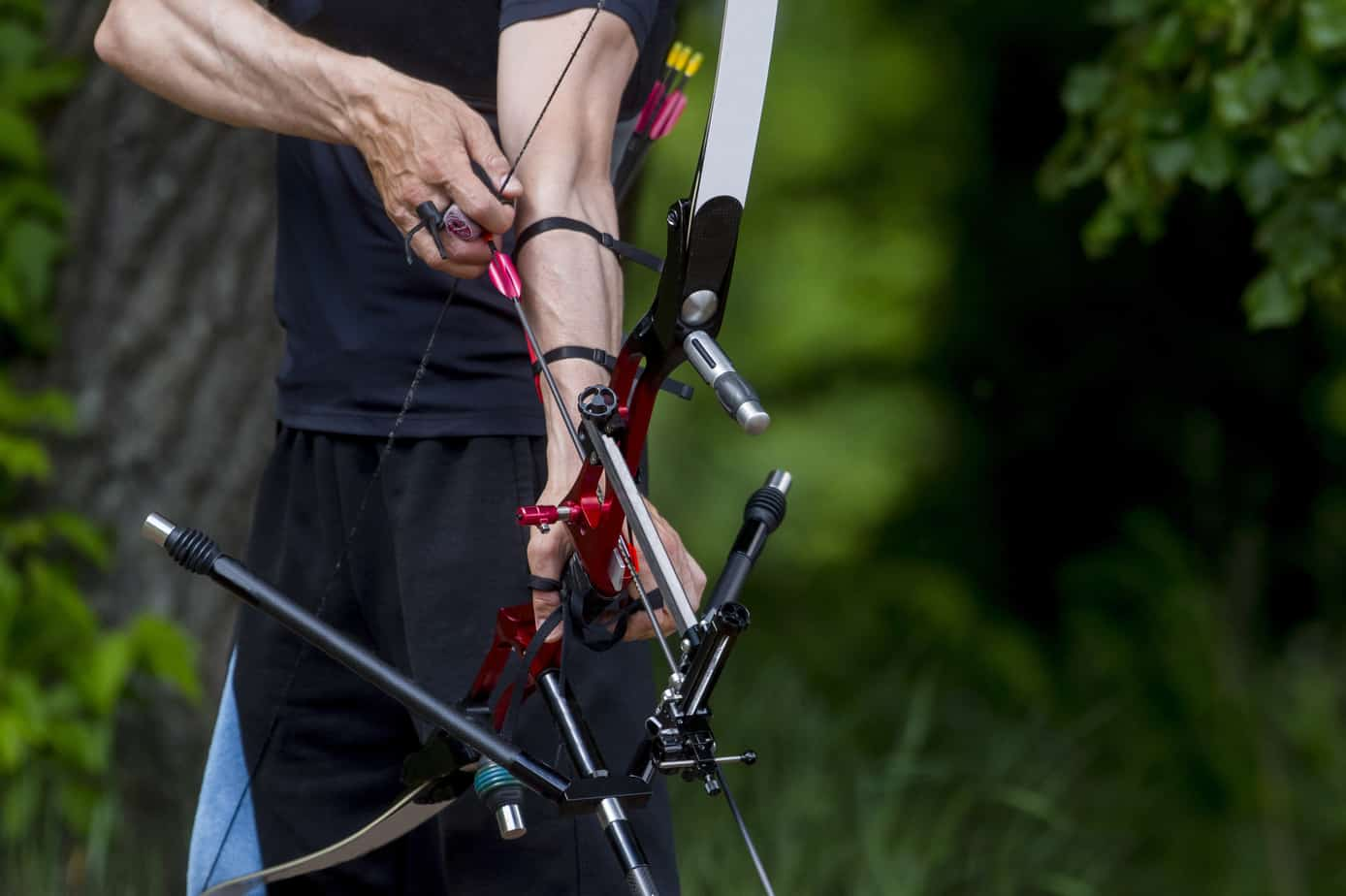 Archer pulls on the sport bow string, taking aim at his target at the competition. Male, concentrated.