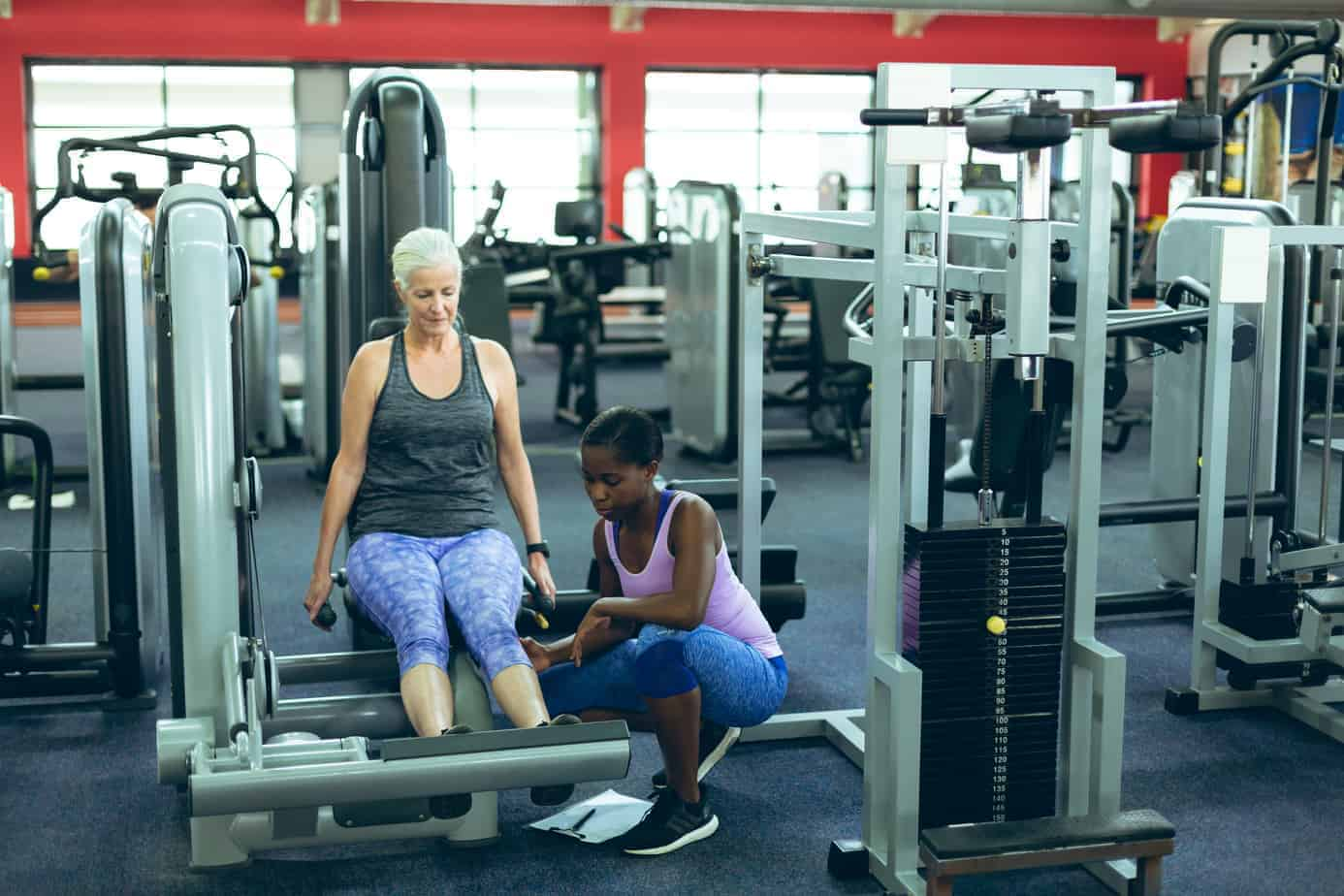 Female trainer assisting active senior woman to work out on leg curl machine.
