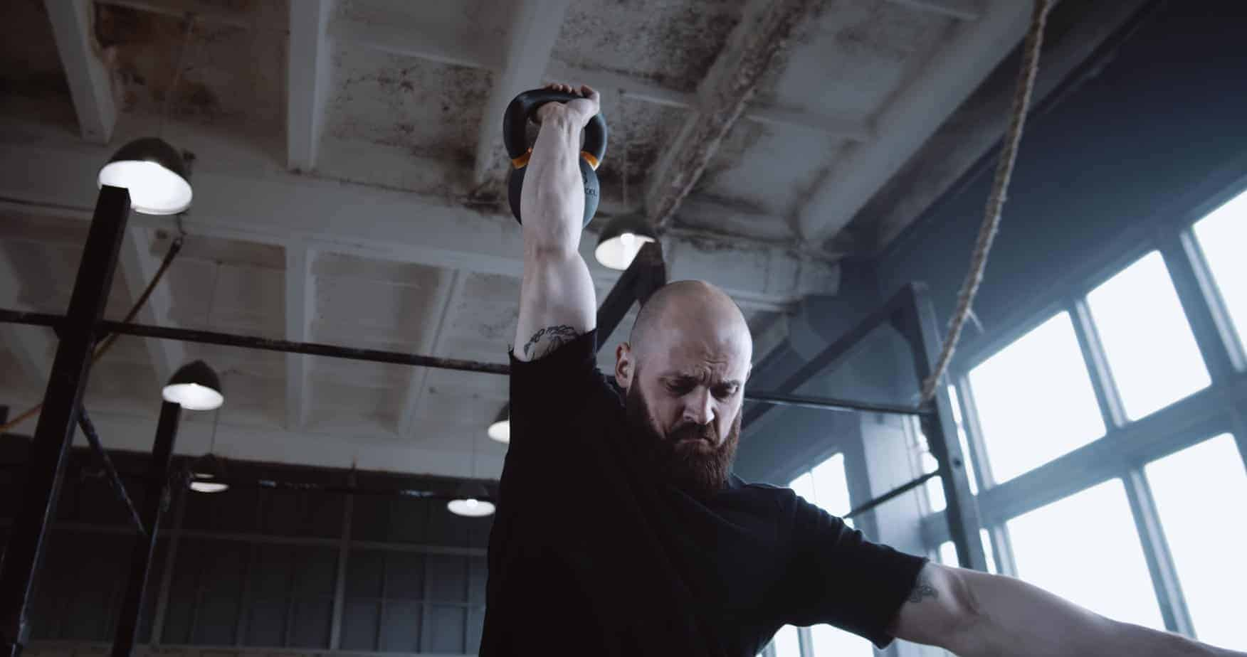Athletic young tough Caucasian man working out, lifting kettlebell during functional training in large gym slow motion.